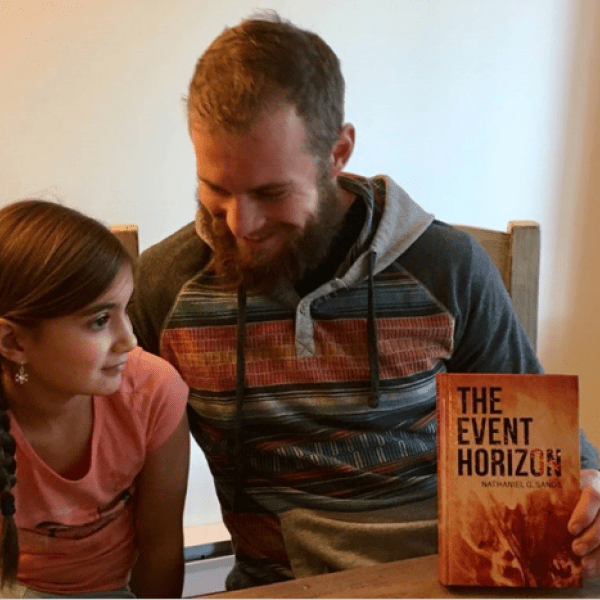 Nathaniel with his daughter and his book